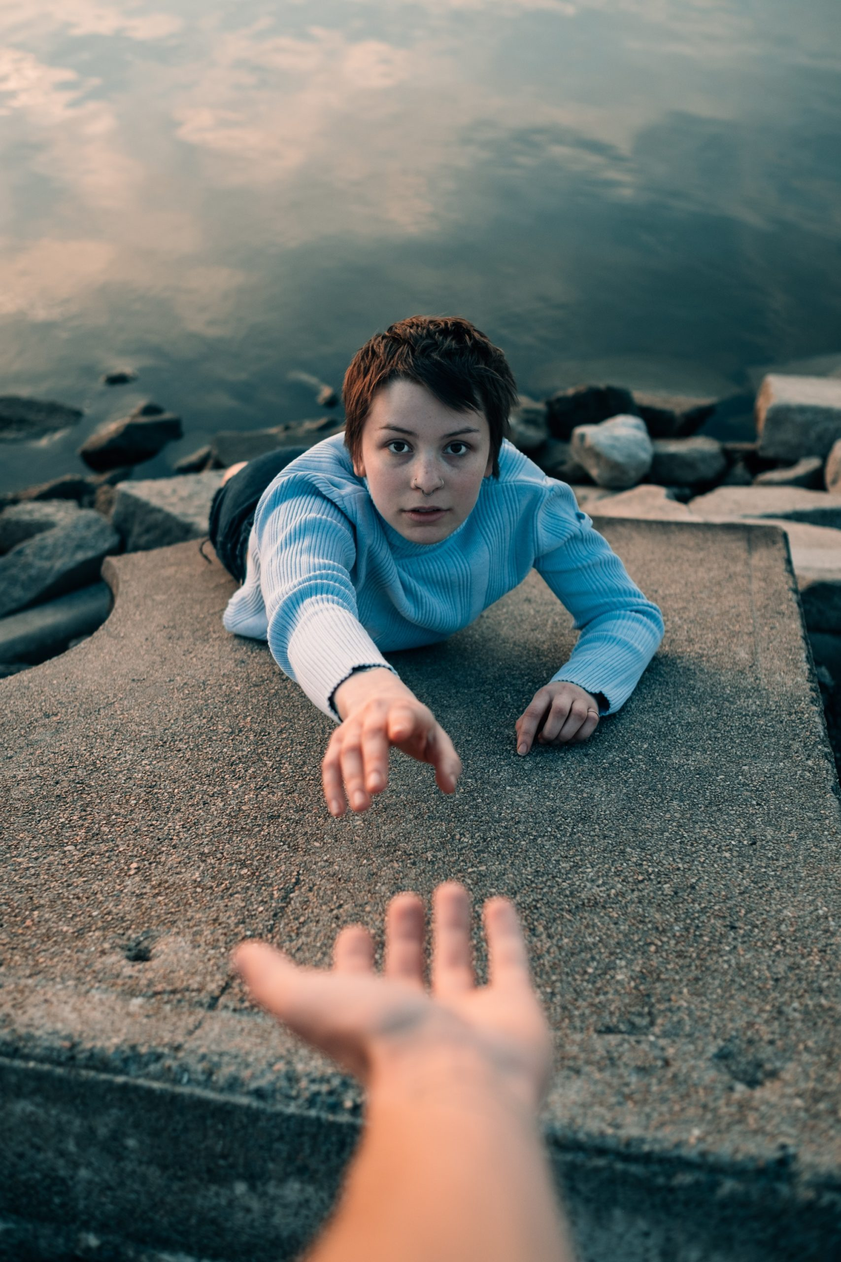 A person with short brown hair and a bright blue sweater stands on a ledge above water, extending their hand up, asking for help, as another arm reaches down towards them to help them up.
