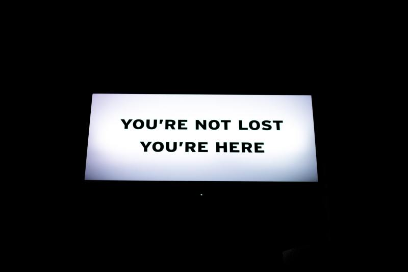 A white glowing sign that says in black simple letters 'You're not lost. You're here.""