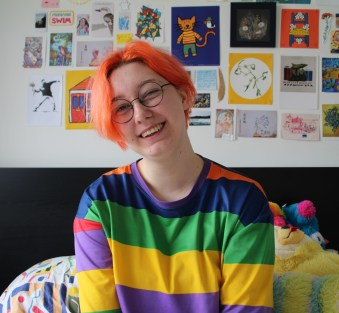 A light skinned person with short bright orange hair, black circular glasses, and a rainbow striped shirt on. They are sitting on their bed and stuffed animals and many small pieces of artwork are behind them on the wall. They are smiling cheerfully and tilting their head to their right slightly.