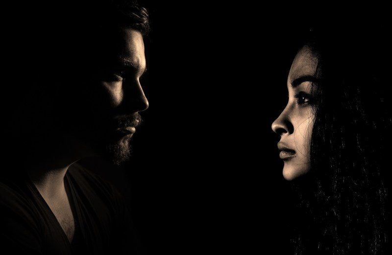 A very dimly lit photo of a man and a woman's face, seen from the side. They are facing each other, but staring into the distance as if they don't see each other.