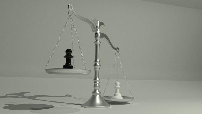 A silver two-sided balance scale holds a black chess piece on one side and a white chess piece on the other, the white chess piece weighing much more heavily despite being the same size.