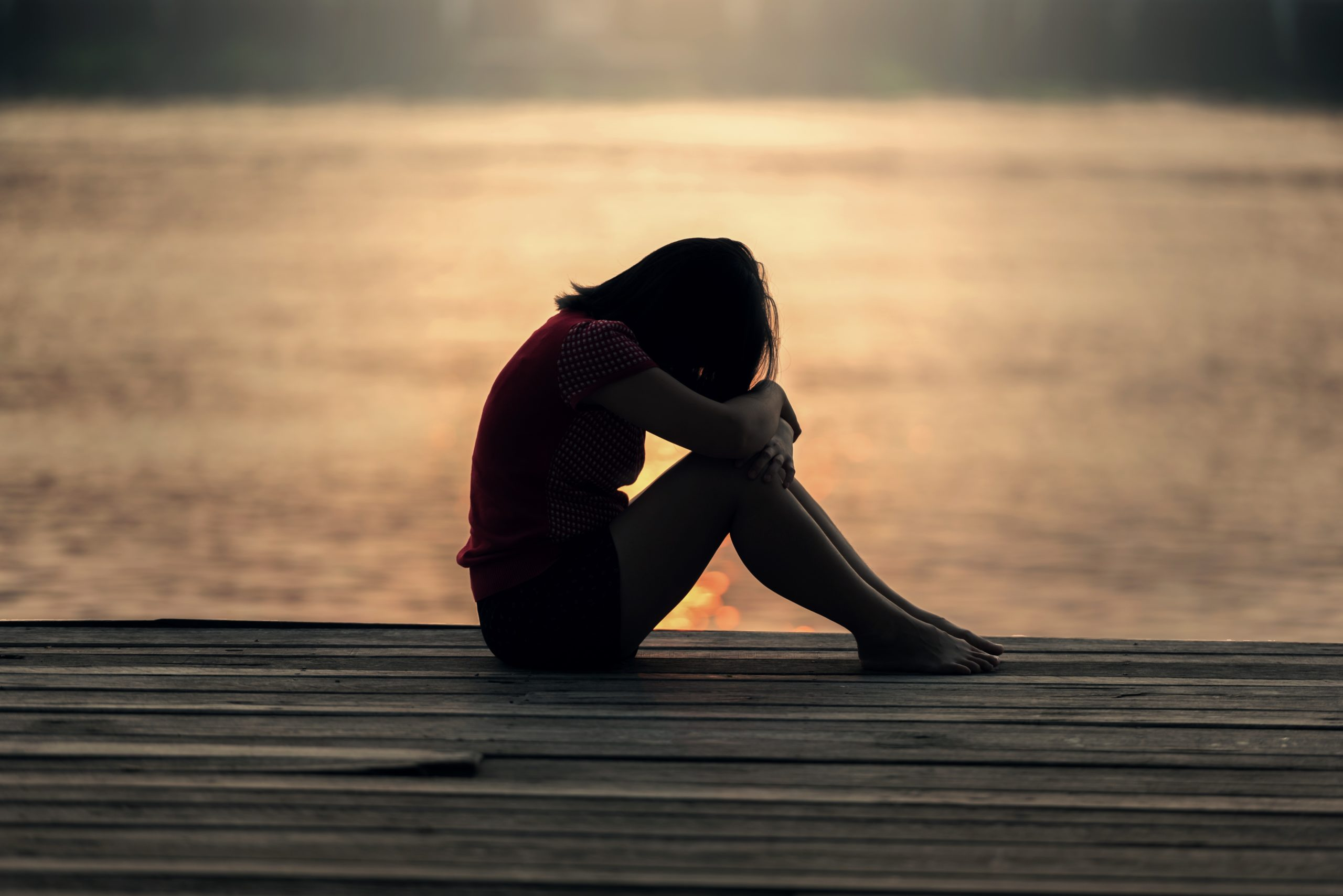 A woman sits on a wooden deck next to the ocean, back lit by the sunrise. She is hunched over her knees as if she is crying.