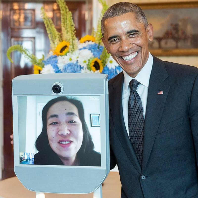 President Obama poses for a photo next to a live video feed of Alice Wong, smiling at the camera. Behind them is a large bouquet of yellow, white and blue flowers.