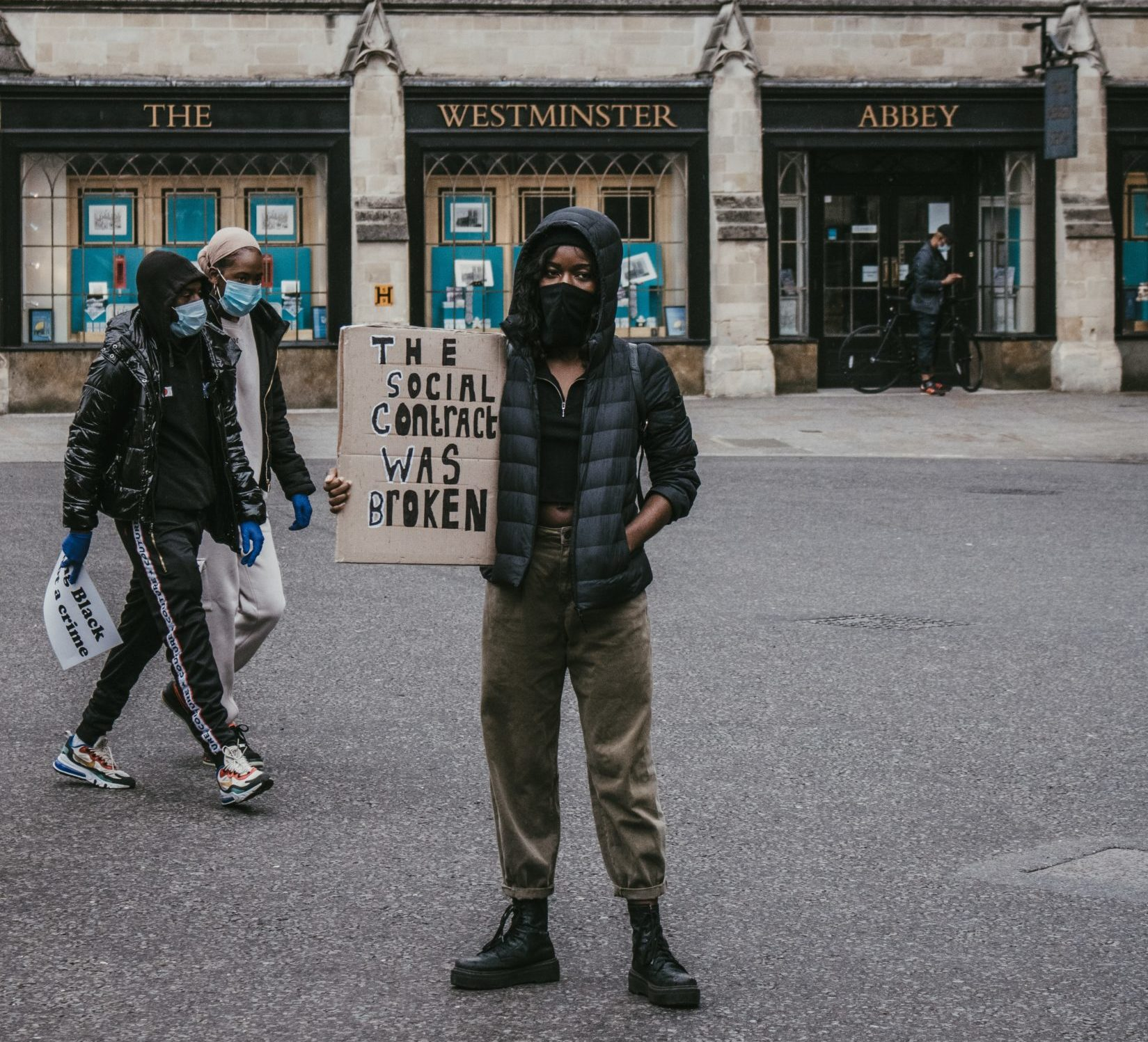 "A black person wearing a black face mask, a black puffy jacket with the hood up, a black shirt, cargo pants, and black boots stands in front of the bottom floor of the Westminster Abbey, holding a sign that says ""The social contract was broken"""