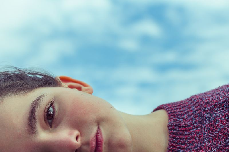 A light skinned young person lies down staring at the camera so that only her mouth, nose, and left eye is visible. She is wearing a purple sweater and there is a blue sky with white clouds behind her.