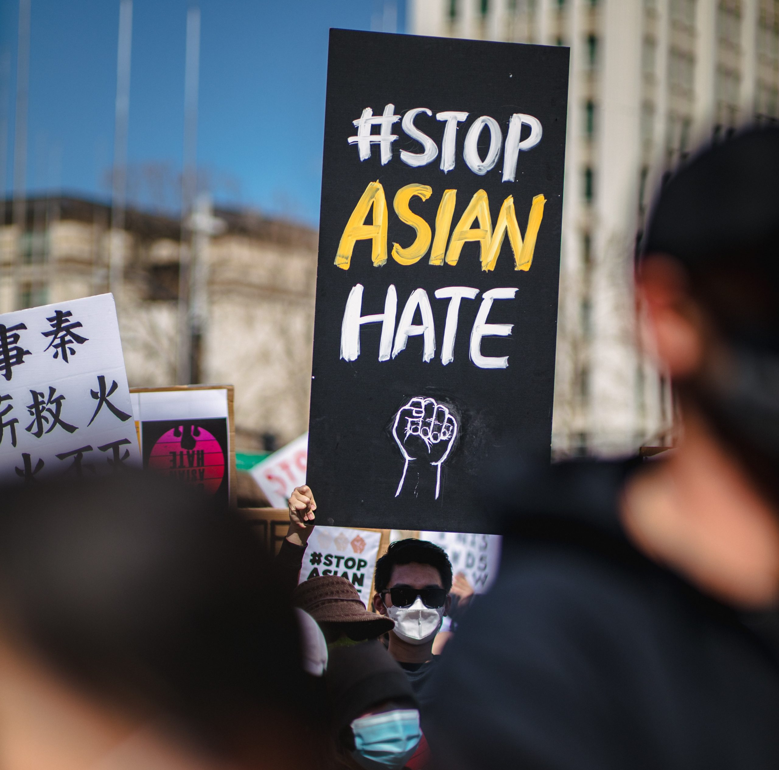 """A man with pale skin, black short hair, dark sunglasses, and a white mask stands in a crowd of protestors holding a rectangular black sign that says in all caps white and yellow letters """"#Stop Asian Hate"""" with an outline of a fist below it.t"""