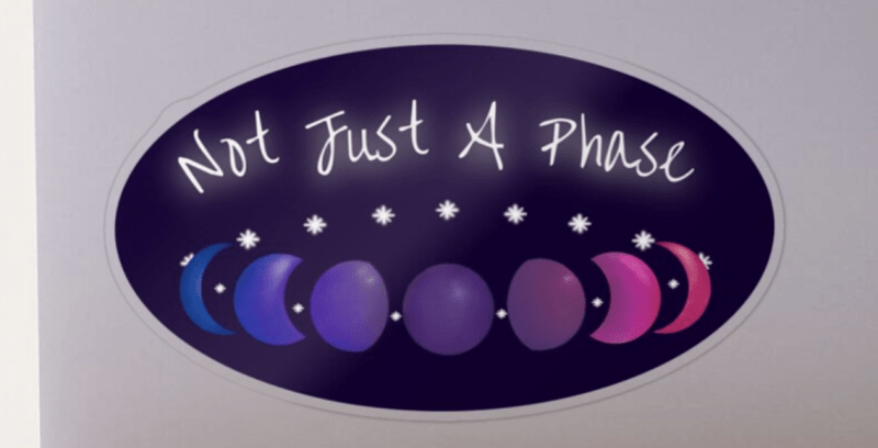 """A ring made of white stars and the phases of the moon floats under the white glowing words """"Not Just a Phase."""" The moons are colored in a textured gradient with the colors of the bisexual pride flag. The design is demoed on a dark purple oval sticker on a silver laptop."""