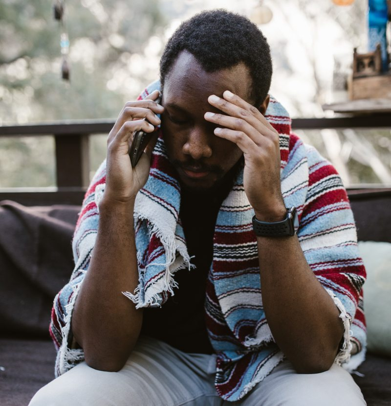 A man with dark skin and short black natural hair sits on an outdoor couch, his elbows leaned on his knees, his head to his forehead, focused on a difficult phone call. He has a rough blanket wrapped around his shoulders that is stripes of pale blue, dark red, black, and off white.