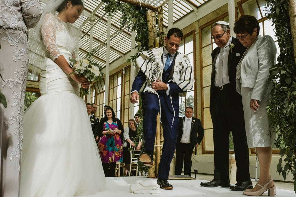 Groom, surrounded by family and watched by his bride, raises his foot to smash the glass at a Jewish wedding in London's Kew Gardens