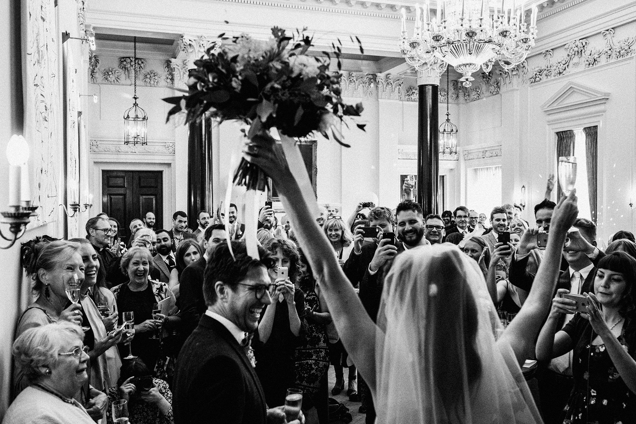 The Ned wedding reception black and white bride holding her bouquet above her head. Bride and groom entrance
