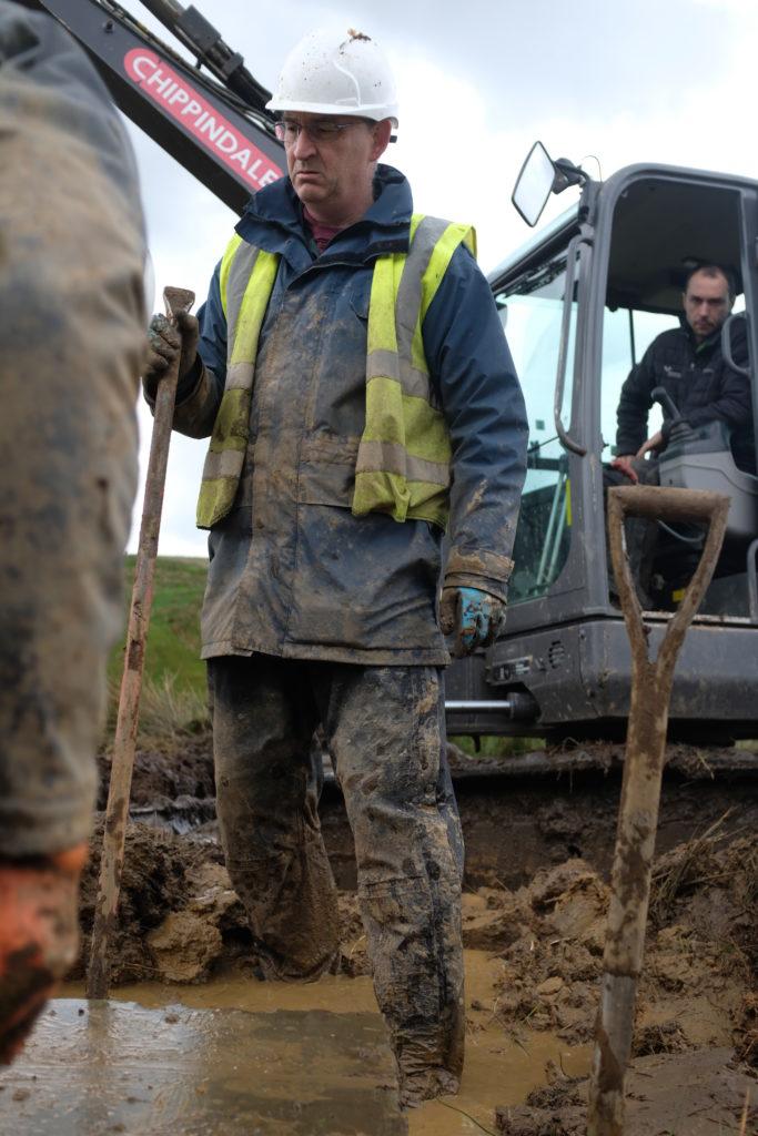 Volunteer Clive Herdman deep in mud