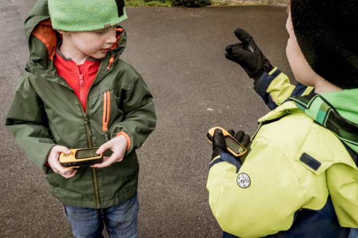 Two children hold GPS receivers on a geocaching search