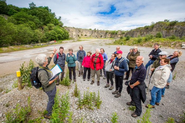 Group of people being led by a Dales Volunteer at Threshfield Quarry