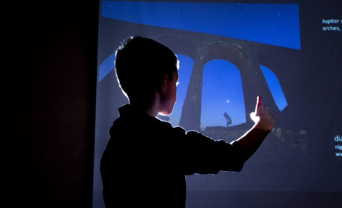 Young boy pointing at Ribblehead Viaduct at night on a big projector