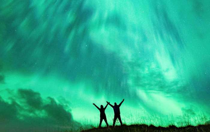 Two people stood with their arms in the air under the Aurora by Jacqueline Garellick