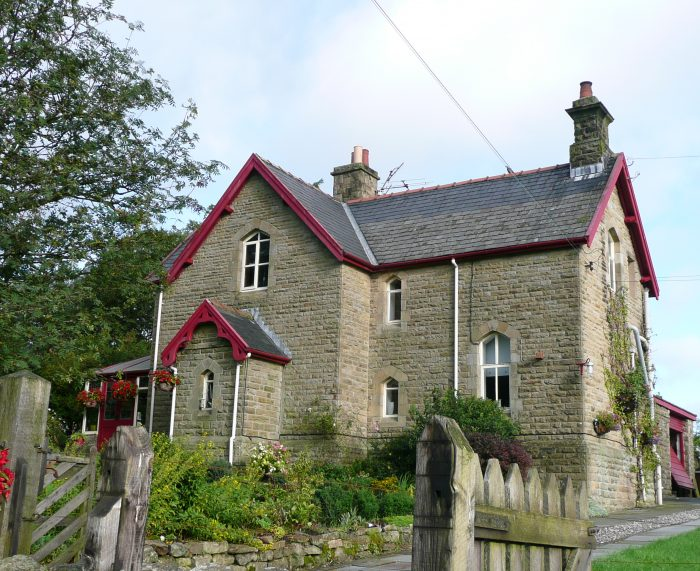 Photo shows the Station  Masters' House at Hrton-in-Ribblesdale. Unusually the bargeboards are painting Midland Railway maroon instead of cream. Aside from that, the house is stereotypical with specified chimneys and a porch