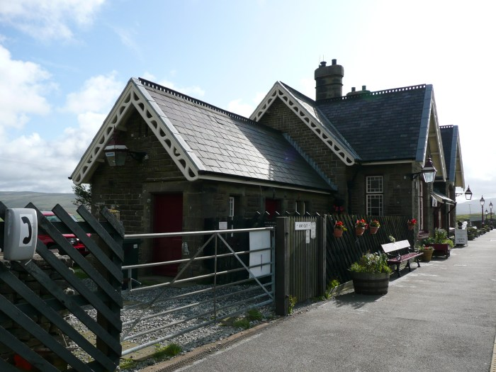 Photo shows the booking hall at Ribblehead Station. The building is a copy of others along the line, including Dent and Garsdale Head. It i coloured maroon and cream and is built of rusticated limestone