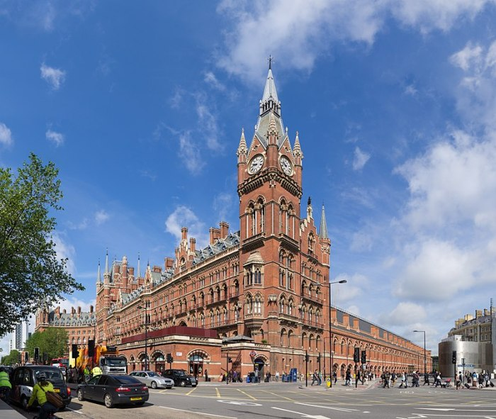 Photo shows London's St Pancras Station on a sunny day. The clock tower is against a blue sky