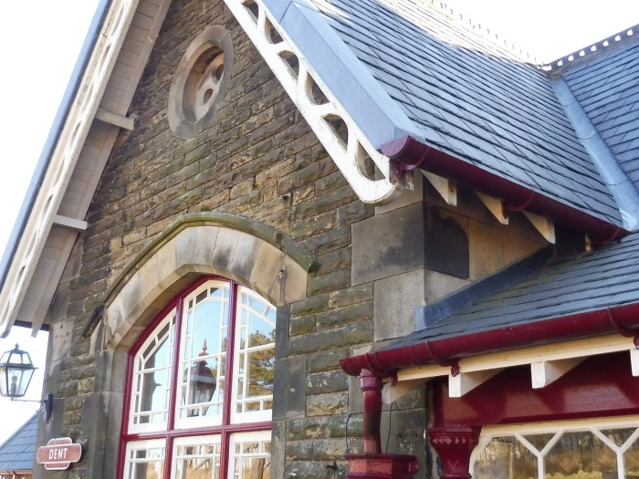 Photo shows a close up of Dent booking hall. The classic Midland Railway bargeboards (cream) and casement windows (maroon frames) are visible