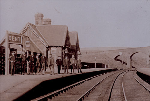 Photograph is an old image of Dent Station. Some passengers wait on the platform in front of the booking hall, which looks much the same today as it did then