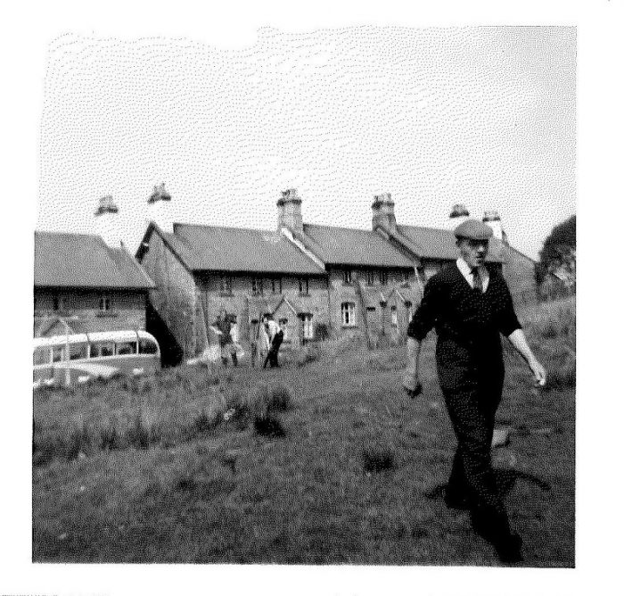 Photograph is black and white. It shows a local man walking across the drying area in front of Garsdale cottages.