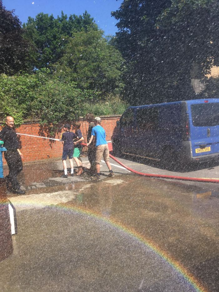Young Rangers help each other spray the fire engine's hose.