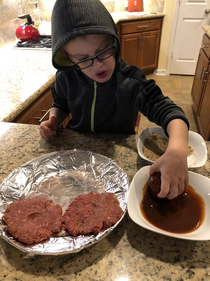 Young boy rolling burger meat in a bowl of bbq sauce