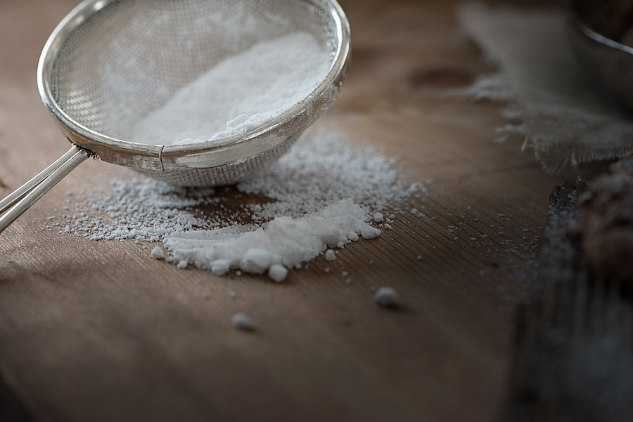 Commonly Confused Cooking Terms: Baking soda in a small metal strainer with more baking soda on the bamboo surface