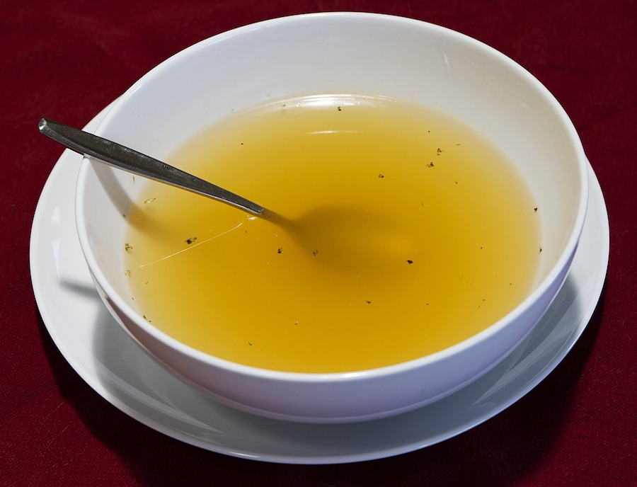 Anti-inflammatory bone broth in a white bowl on a white plate on a red surface