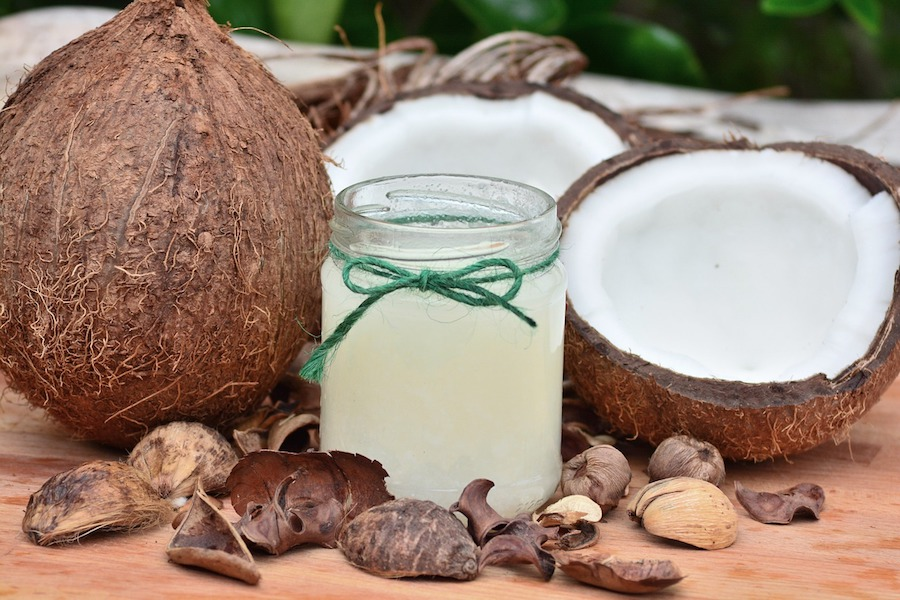 Anti-inflammatory coconut oil in a glass jar surrounded by coconuts