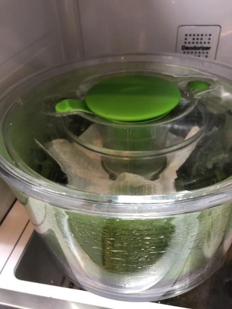 Salad spinner full of lettuce in a refrigerator