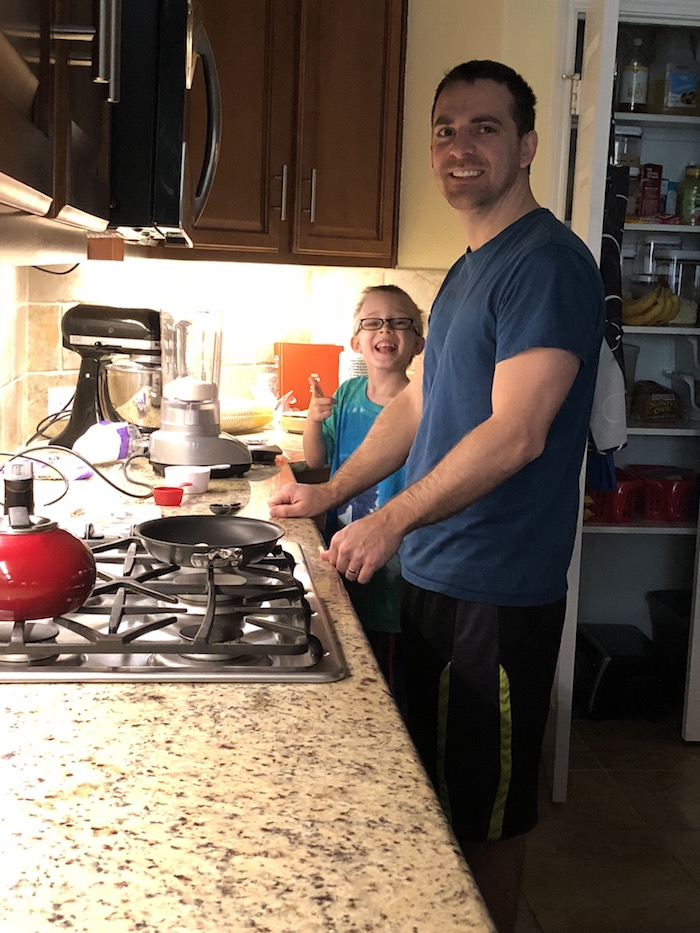 Man and young boy standing in the kitchen at the stovetop with the blender and crepe ingredients on the counter