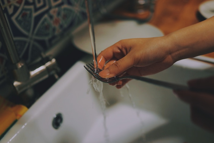Hands cleaning a fork under running water