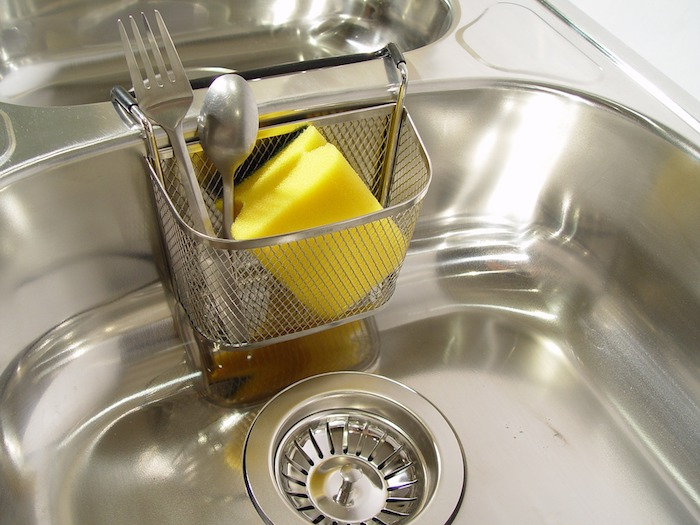 Yellow sponge in a caddy over a stainless steel sink