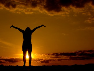 Silhouette with arms raised at sunset