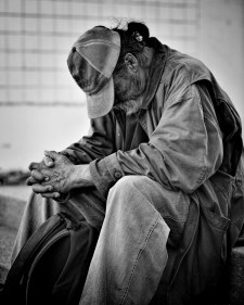 homeless man with head down in black and white