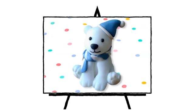clay sculpted white polar bear with blue hat and blue and white scarf