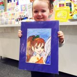 student holding new art in a small matte