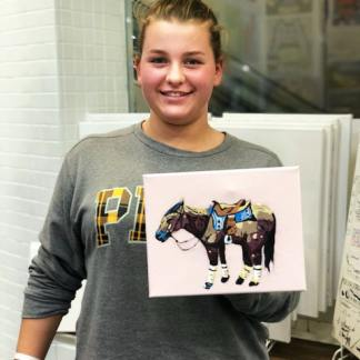 student holding 8x10 canvas