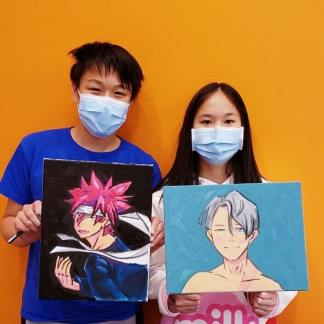 2 students holding paintings of anime characters