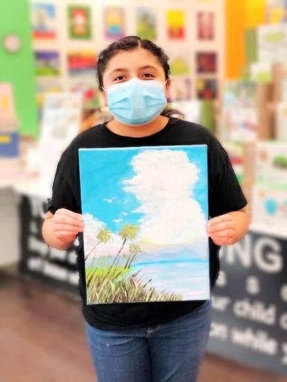student holding painting of beach scene