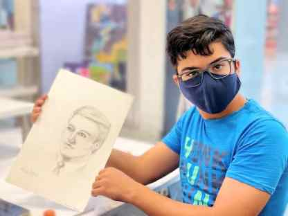 boy holding sketch of a face