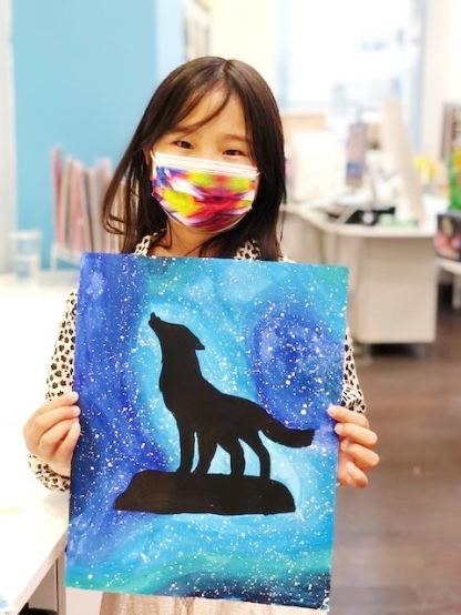student holding painting of a wolf