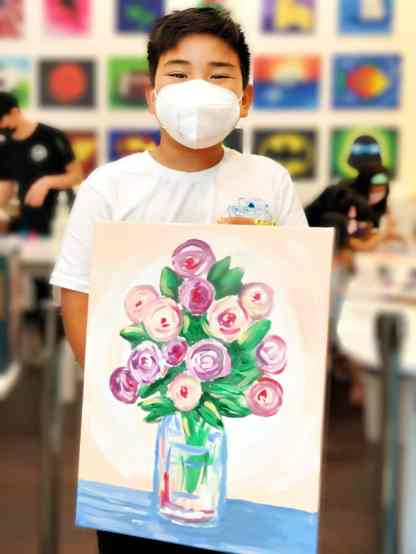 student holding painting of vase of flowers