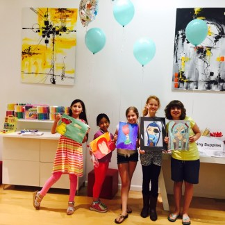 5 girls holding their art with balloons behind them