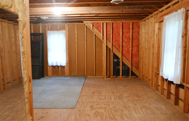 Unfinished attic storage room with exposed studs and curtained windows