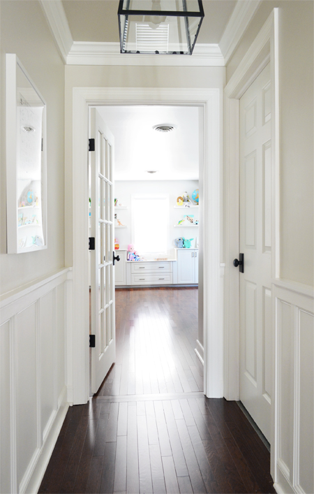 View into a bonus room playroom from hallway with white wainscoting and continuous wood flooring