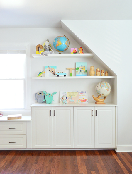 White floating shelves hung against angled wall and sloped ceiling in kids playroom bonus room
