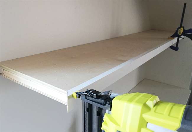 A Ryobi power nailer attaching face pieces of 1x2 pine wood board to thin white floating shelves in bonus room