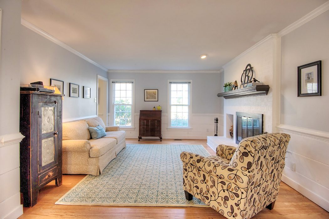 living room staged to sell with neutral walls white fireplace and minimal furniture
